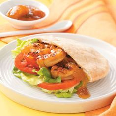 Mango Shrimp Pitas Recipe -Mango, ginger and curry combine with a splash of lime juice to coat this juicy, grilled shrimp. Stuffed in pitas, the shrimp combo makes for an easy-to-hold, fabulous entree! You could also serve on a bed of rice for a less casual presentation. —Beverly O'Ferrall, Linkwood, Maryland