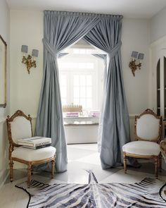 Glam French foyer with floor to ceiling blue silk panels covering doorway with transom window. Gold French chairs upholstered in white fabric and antique brass French sconces with blue pleated shades. Via Decorpad.