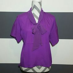 "Lovely violet blouse NWT Brand new with tags  Gorgeous violet blouse with tie detail at neckline.  Pair with jeans or leggings and sassy heels for a fabulous outfit!  Size small 96%polyester 4%spandex Length in front approx 23"", length in back approx 28"" Bust approx 20.5""  ❤No trades  ❤Price is firm unless bundled Tops Blouses"