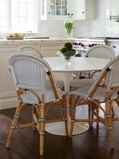 Fabulous eat-in kitchen features a marble Saarinen Dining Table lined with black and white French bistro chairs, Serena & Lily Riviera Side Chairs.