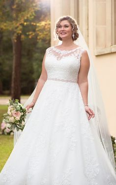 This traditional ball gown plus size wedding dress from Stella York features lace over tulle in a soft A-line silhouette, perfect for the classic bride! The voluminous skirt feels full and flowy while remaining light-as-air as layers of tulle are adorned with delicate lace details that give off a unique effect. The illusion lace neckline, that highlights the blushing bride's face, continues to the back of the ball gown where floral patterned lace creates a stunning back.