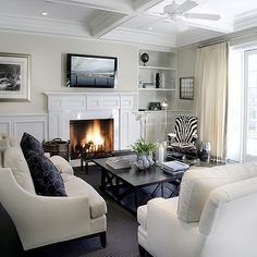 Elsa Soyars - living rooms - wainscoting, living room wainscoting, tv over fireplace, black coffee table, zebra chair, cream sofa, white sofa, cream curtains, cream drapes, coffered ceiling, living room coffered ceiling,