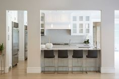 Custom kitchen with white shaker cabinets accented with nickel pulls along with light gray counters and a gray subway tiled backsplash.