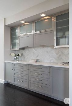 Herringbone Calacatta tile backsplash. The grey painted cabinets have a more modern feel with frosted glass fronts and brushed stainless hardware.