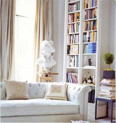 Can see this sofa in parisian living room with light blue and silver throw pillows, in Paris Flat/Loft; white chesterfield sofa