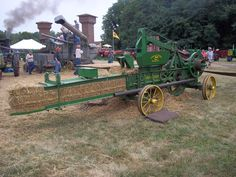 "John Deere stationery baler.  The bales were wire tied with ""baling wire"" by two men who poked and tied the wire.  The long tube above the wheels held the wire."