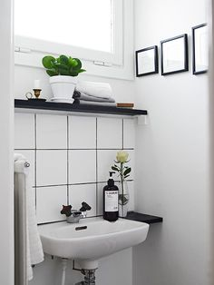 Like the black shelves theyve added as well as the styling. It doesnt take all that much to bring in some colour and some life in a neutral bathroom. - Model Home Interior Design White Tiles Black Grout, White Bathroom Tiles, Laundry In Bathroom, Neutral Bathroom, Bathroom Plants, Basement Bathroom, Washroom, Tiny Bathrooms, Beautiful Bathrooms