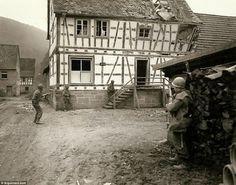 Attention: soldats Septième Armée ont leurs armes à la main comme ils attaquent une maison à Bobenthal, en Allemagne, à la recherche de tireurs d'élite