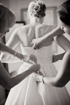a great photo idea – mother of the bride  maid of honor helping with the dress!