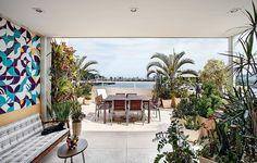 A varanda projetada pela arquiteta Paula Neder incorporou os tons de azul e verde tanto pelo papel de parede escolhido, como pela paisagem que invade o ambiente interno