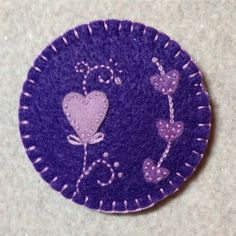 Needle book made from grape purple, medium purple and lavender. This round needle book features a large heart on the front and heart flower on the back cover. It has purple lining and two medium purple circles of felt on the inside to store your needles and pins. Needle books make a nice gift to a stitcher, embroiderer, quilters or anyone that sews! I like to keep one in my grab and go stitching kit, for a little stitch time waiting for school to get out, at games or practice or the long…