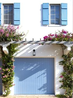 a painted garage door and shutters adds bright color to an exterior