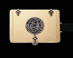 A DIAMOND, RUBY AND ONYX POWDER COMPACT, BY JANESICH   Of rectangular outline, the centre set with an onyx, rose-cut diamond and cabochon ruby circular panel depicting an Oriental garden, with onyx and diamond-set hinges and fastener opening to reveal a fitted mirror, to the black silk handle, circa 1926, 8.0 x 5.5 x 1.5 cm., with French assay marks  Signed by Janesich, Paris, no. 5616
