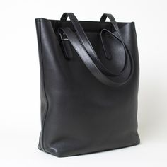 An elegant take on the go-everywhere tote 100% Italian leather exterior Features tonal ultrasuede lining, two canvas pockets with snap closures, and polished chrome hardware at straps and feet To clean, wipe dry with a damp cloth; for best results, apply a leather conditioner and water repellent spray before using and after each cleaning
