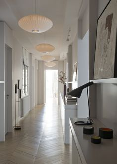 Un long couloir tout blanc, rythmé par de beaux luminaires en coton sur armature métallique. Plusieurs meubles de rangement bas servent de consoles pour disposer livres et vases. Des corniches hautes sont exploitées pour déposer les tableaux.