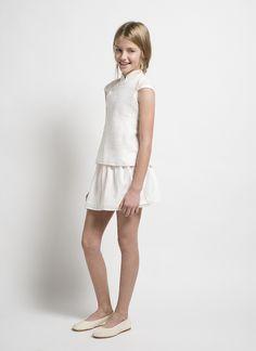 Este conjunto está compuesto por una camiseta con cuello de mao y falda blanca.