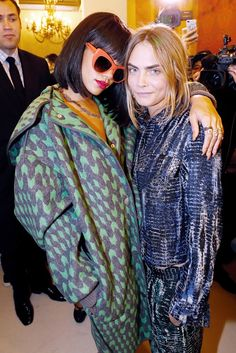 WHO: Rihanna & Cara Delevingne. WHAT: Hanging out backstage at the Stella McCartney F/W 14 show. ​WEAR: On Rihanna: Sabine G. diamond, ruby, and gold necklace. On Cara: Stella McCartney jacket and pants from the F/W 14 collection.