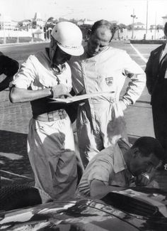 Tony Brooks and Stirling Moss swap notes in the Vanwall pit, Portuguese Grand Prix 1958. Note Brooks' kidney belt...