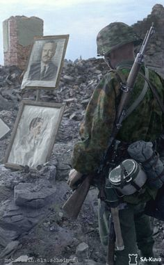"A soldier of the 6th SS Gebirgs-Division: ""Nord"" looks at a portrait of Stalin laying in the rubble of a bombed out Soviet city somewhere in the USSR."