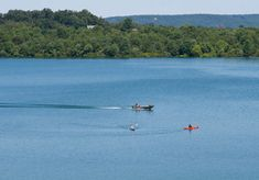 A fishing boat motors by tw0 kayaks on the blue lake at Codorus State Park, Pennsylvania.