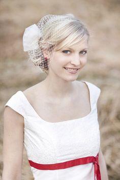 kurzes brautkleid mit empire linie, rot- pinkem band zum binden unter der brust, zarte bestickung im oberteil mit trägern (www.noni-mode.de - Foto: Hanna Witte)