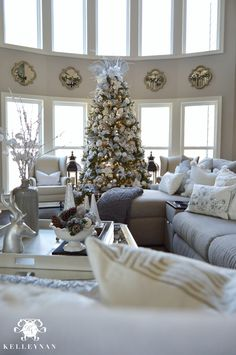 Two story living room with neutral, silver, and gold Christmas decor and large silver and gold Christmas tree in bow of windows . Christmas tree with lanterns and quatrefoil mirrors between windows