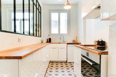 Dans cette cuisine semi-ouverte, du carrelage imitation carreaux de ciment a été choisi. De quoi donner cachet et relief à la pièce !