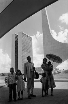 Magnum Photos -  Rene Burri BRAZIL. Brasilia. 1960. Worker from Nordeste shows his family the new city on inauguration day. In the background: the National Congress building by Oscar NIEMEYER.