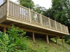 """Deck overlooking the pool area.  """"A deck sorts out the problem of slopes in the garden. No expensive groundworks and levelling - just build a deck like this one."""""""