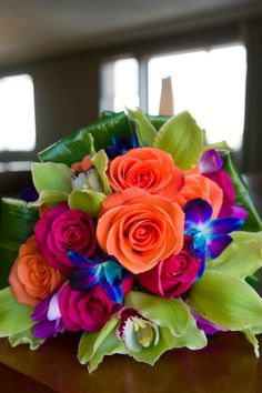 Tropical Bouquet of green cymbidium orchids, blue dendrobium orchids, orange and hot pink roses by Iza's Flowers, Inc. www.weddingsbyiza.com