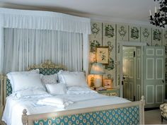 An antique French wallpaper design covers the walls in this master bedroom. The bed is accented with a hand-smocked half canopy of sheer Swiss Batiste and the headboard and foot board are covered in traditional blue upholstery.