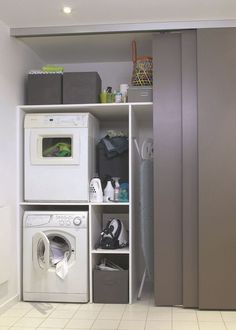 Stacked washer drier with pull out shelves for glass jars filled with laundry soap pods and drier balls, and one long spot for hanging iron with short cubby to store iron above. And one cubby to store laundry basket. Close with hanging/sliding barn door.