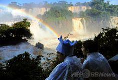 南米ブラジルのフォス・ド・イグアス(Foz do Iguacu)で、豪雨で増水した世界遺産「イグアスの滝(Iguazu Falls)」にかかる虹を眺める観光客(2014年6月12日撮影)。(c)AFP/Norberto Duarte ▼13Jun2014AFP|濁流にかかる虹、ブラジル・イグアスの滝 http://www.afpbb.com/articles/-/3017614 #Iguazu_Falls #Rainbow #Arco_iris #Arc_en_ciel #Regenbogen #Pelangi #Regenboog #Tecza #Gokkusagi