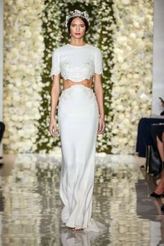 A two-piece silk sheath wedding dress by Reem Acra, with a short sleeve crop top and floral embellished details.