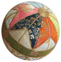 Vintage Kimekomi temari made from kimono remnants. Kimekomi means 'tuck in' in Japanese, and this gives you a clue as to the method of this ball's manufacture. The core of the ball is made from wood or compressed sawdust, with the design being carved into it to allow the fabric pieces to be tucked in to form the desired pattern.