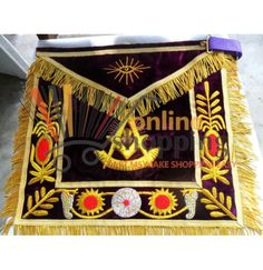 HAND EMBROIDED MASONIC GRAND PAST MASTER APRON PURPLE PRODUCT DESCRIPTION:      ITEM CONDITION NEW     HAND MADE APRON WITH FLAP EMBROIDED WITH GOLDEN BULLION WIRE & THREAD.     APRON BODY AND FLAP MADE WITH HIGH-QUALITY PURPLE VELVET.     SIZE 35.5 x 39 CM, FRINGES EXCLUDED.     4 CM WIDE GOLD BULLION FRING IS COVERING ALL APRON AND FLAP TRIMMED WITH QUARTER INCH GOLDEN BRAID.     5 CM WIDE PURPLE VELVET BODY BORDER.     SQUARE, COMPASS, SUN AND EYE IS HAND EMBROIDED WITH GOLDEN BULLION…