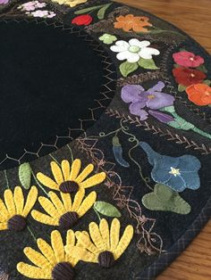 "Wool appliqué with crazy quilt stitching. Hand stitched by MaryAnnThom. Adapted from ""Flower Garden Crazy Tablemat""by Primitive Gatherings."