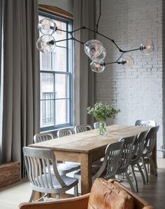 Dining room with ceiling to floor curtains, chandelier, white painted brick walls.