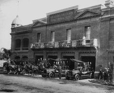 Central Fire Station, Brisbane, Queensland, ca.1900 -  Double storey brick building, with small balconies on the first level leading from open doors on the front of the building. Two fire trucks are parked in front of the station equipped and ready for work with firemen in uniform standing by.