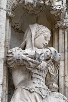 Beautiful statue of young woman in medieval dress on the wall of gothic building in Grand Place in Brussels Stock Photo