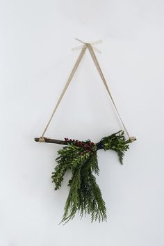DIY modern Scandinavian Christmas wall hanging with evergreen branches