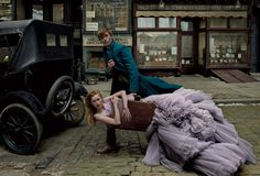 Packing Light - Newt Scamander (Eddie Redmayne) makes his first trip to New York City with model Rianne Van Rompaey, in a sugar-spun, confectionary Giambattista Valli Haute Couture dress; giambattistavalli.com. Photographed (throughout) on the set of Fantastic Beasts and Where to Find Them.Fashion Editor: Grace Coddington