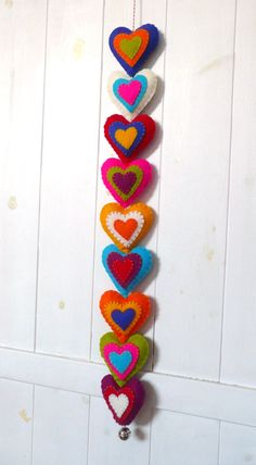 This colorful felt garland makes a lovely present for yourself or a loved one to decorate a wall, a door or a cupboard with. It would make a lovely present for Valentines Day. The 9 hearts (about 7cm tall) are hand cut, made from 6 layers of soft and beautifully colored wool felt and are delicately embroidered on both sides. They can be moved along the appr. 1m long string of red and white bakers twine, so you can change the distance between the hearts. The wall hanging is finished of with a…