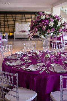 Magenta Tablecloth- Clear Chiavari Chairs and clear candelabra with flowers.