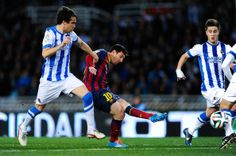 Lionel Messi of FC Barcelona scores the opening goal next to Mikel Gonzalez Martinez of Real Sociedad during the Copa del Rey Semi Final second leg between Real Sociedad and FC Barcelona at Anoeta Stadium on February 12, 2014 in San Sebastian, Spain.