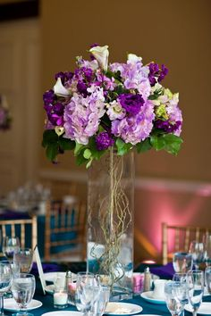 Tall centerpieces could be dramatic! I love a see-through vase, though, so guests can talk across the table. I'd add in tall curly willow branches coming out the top, too, with purple orchids tied here and there. The goal is in the end, to have dramatic arrangements that aren't so round and perfect.