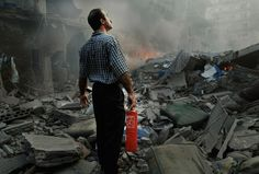 A man looks in despair at the rubble of a six storey apartment building just after it was bombed, realising his small fire extinguisher is not going to be of any use. The building, which was attacked by the Israeli air force, was in the middle of a densely populated area in the city of Tyre. Three casualties were reported.