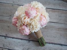 A beautiful shabby chic bouquet with a vintage feel. Eighteen ivory and blush pink roses and peony buds are accented with ivory hydrangeas and tied