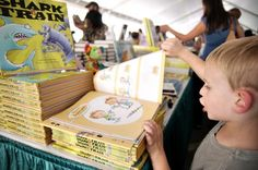 """Hayden Moore, 5, peruses children's books during the 15th annual Texas Book Festival [in October 2010]. The weekend-long event, which attracted thousands of visitors, featured lectures by hundreds of local and national authors, live music, food vending and children's activities."""