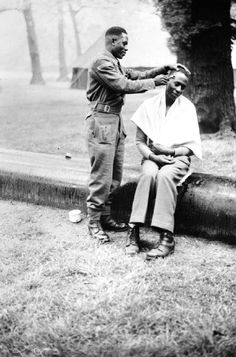 A soldier of the Kings African Rifles practices his barbering skills, at their camp in Kensington Gardens, London - 1946